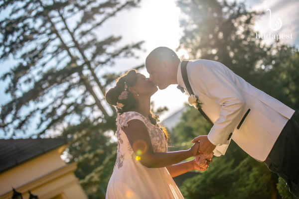 Creative photoshoot with bride and groom, kissing in front of the Paradsasvar Castle Hotel