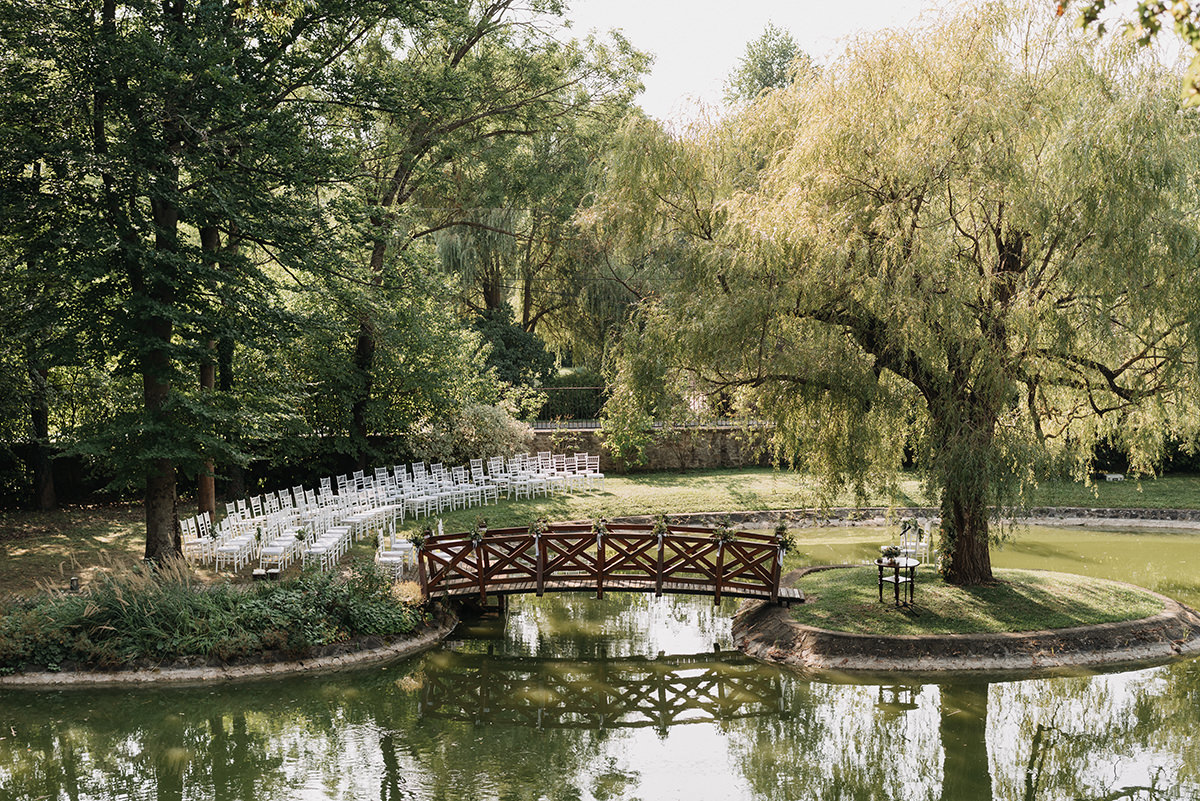 Wedding ceremony set up with white chiavari chair chairs by the lake