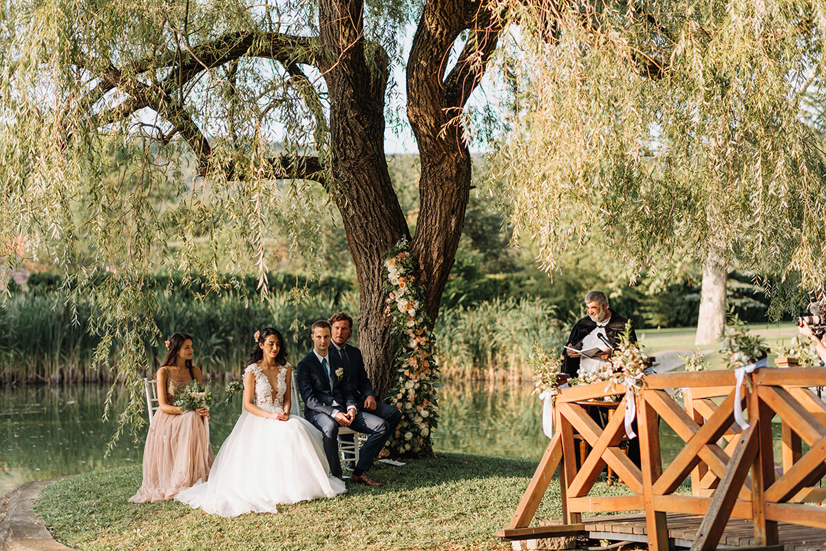 Bride and groom are having their wedding ceremony on a small island surrounded by the lake
