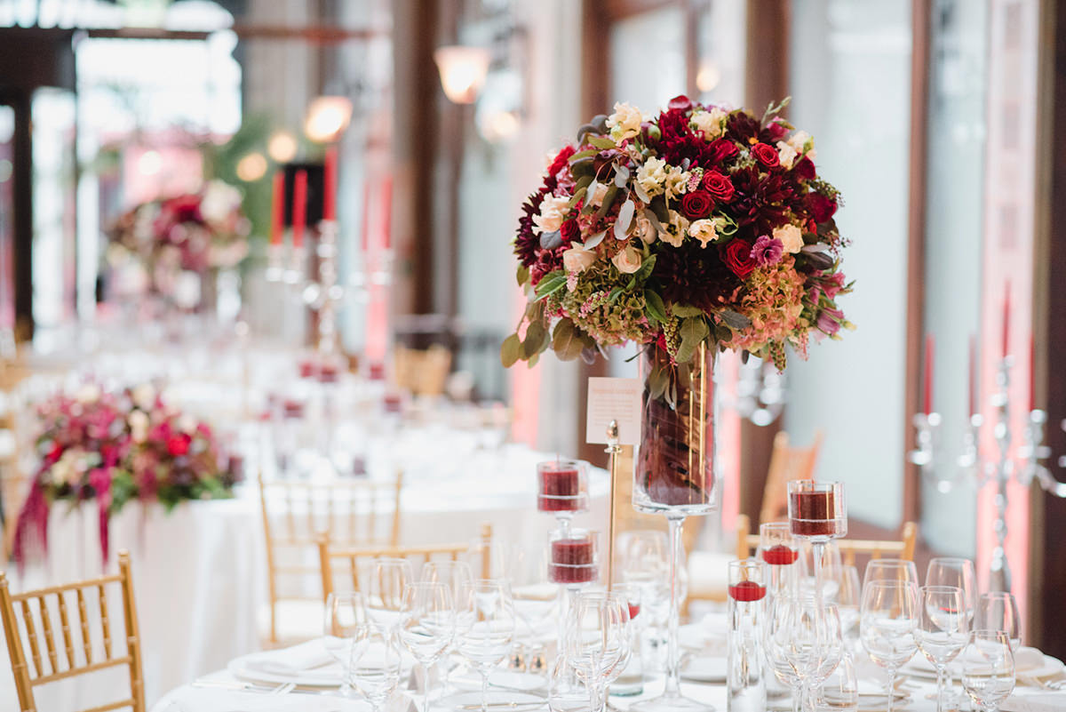 Very bright, red tall centrepiece with red candles and tea candles and golden chivari chairs in the Four Seasons Hotel