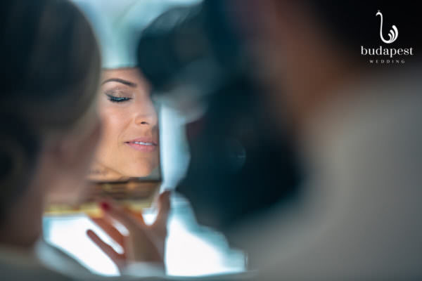 Final touch of the bridal make up while photographer taking pictures of the details