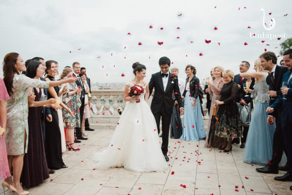 Couple surrounded with their guests in rose petal showers up in the Buda Castle, Savoy Terrace