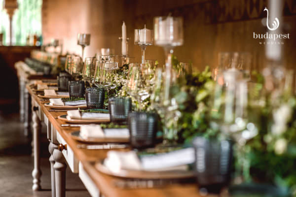 Green wedding decoration alongside the long rustic table with candles