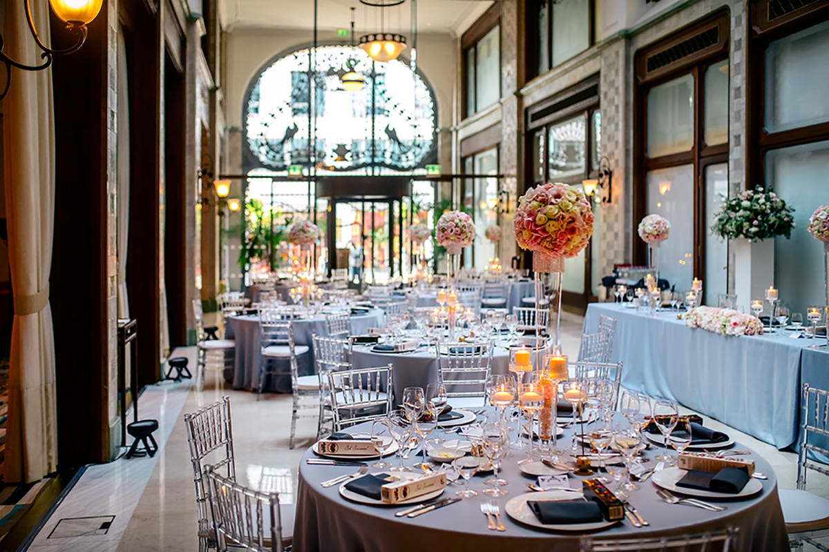 A wonderful wedding decoration with silver table cloths, white and powder pink round shape centrepieces and transparent chiavari chairs
