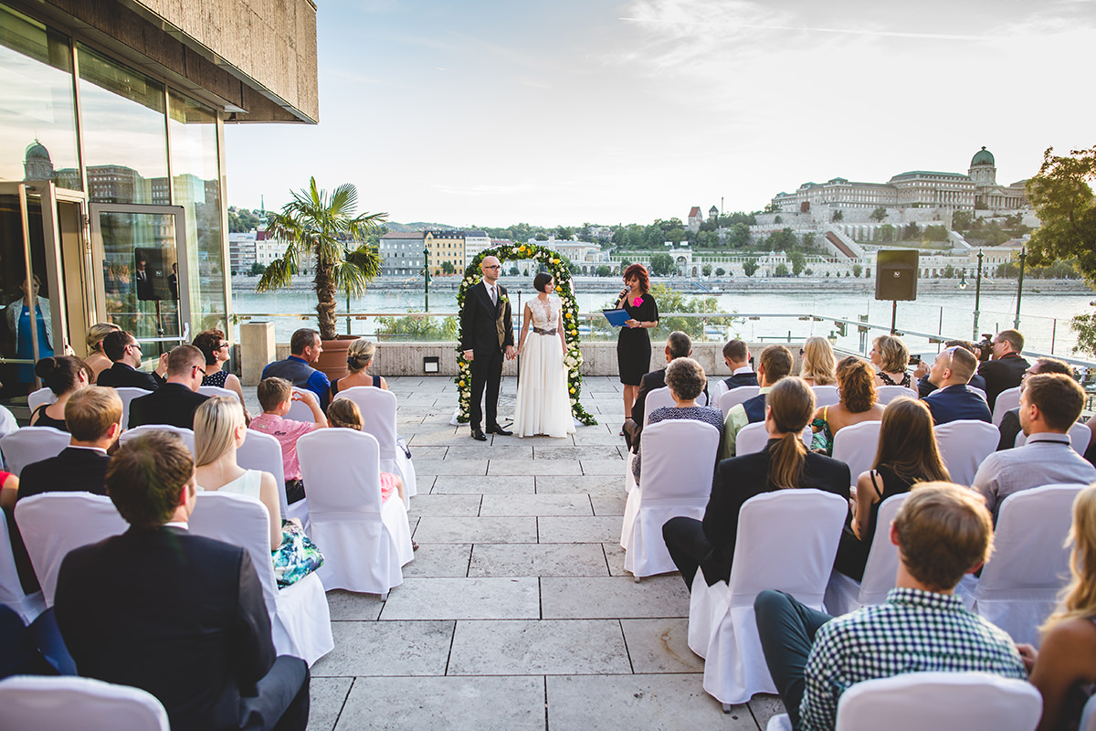 Wedding ceremony with the wedding couple and their beloved guests on the terrace of the Budapest Marriott hotel, background view over the Buda Castle, Hungarian National Gallery