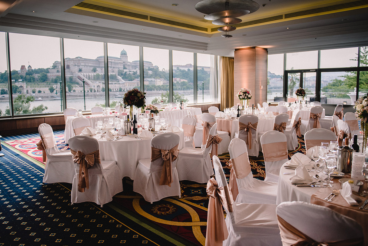 Lighter colour of wedding set up with higher centrepieces and white tablecloths, chairs and soft pink