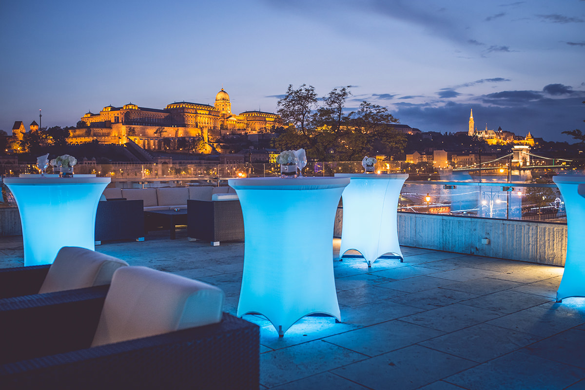 Blue hour with LED lighted cocktail tables on the terrace of the Marriott Hotel, while in the background the Hungarian National Gallery and the Buda Castle can be seen