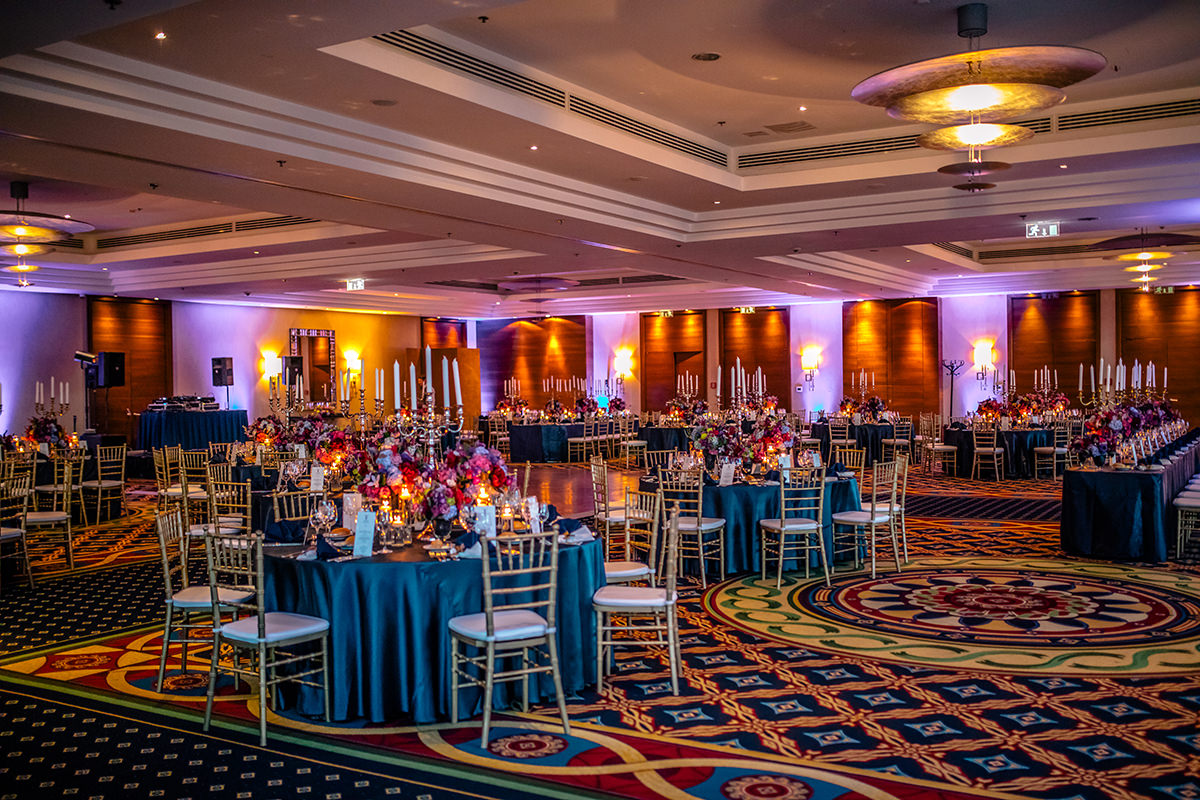 The entire wedding concept was given by the harsh colour of the carpet, yellow, red and blue. Therefore we have chosen navy blue silk table cloths, golden chiavari chairs and matching flower decoration. The candles were perfect final touch to the design in the Budapest ballroom of the Marriott Hotel.