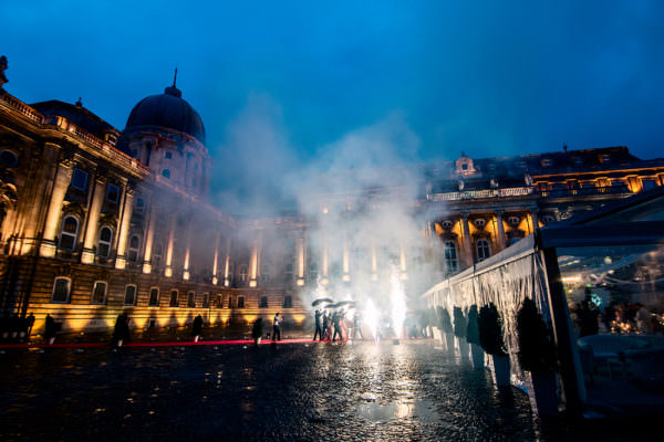 As the bride and groom walking down the aisle on the red carpet the shower firework lights up the Lions' Court, Buda Castle with the background of the Hungarian National Gallery