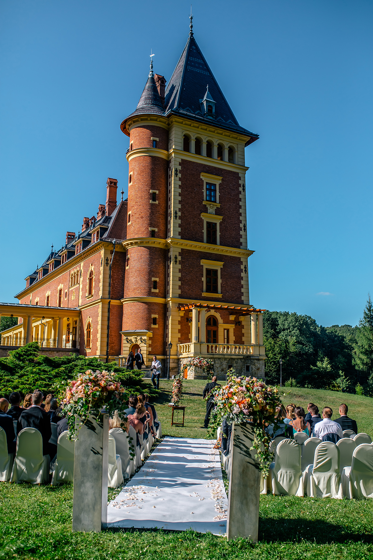 Wedding ceremony and white carpet with the main building of the Castle Hotel Paradsasvar in the background. Ceremony is about to start outside in the garden