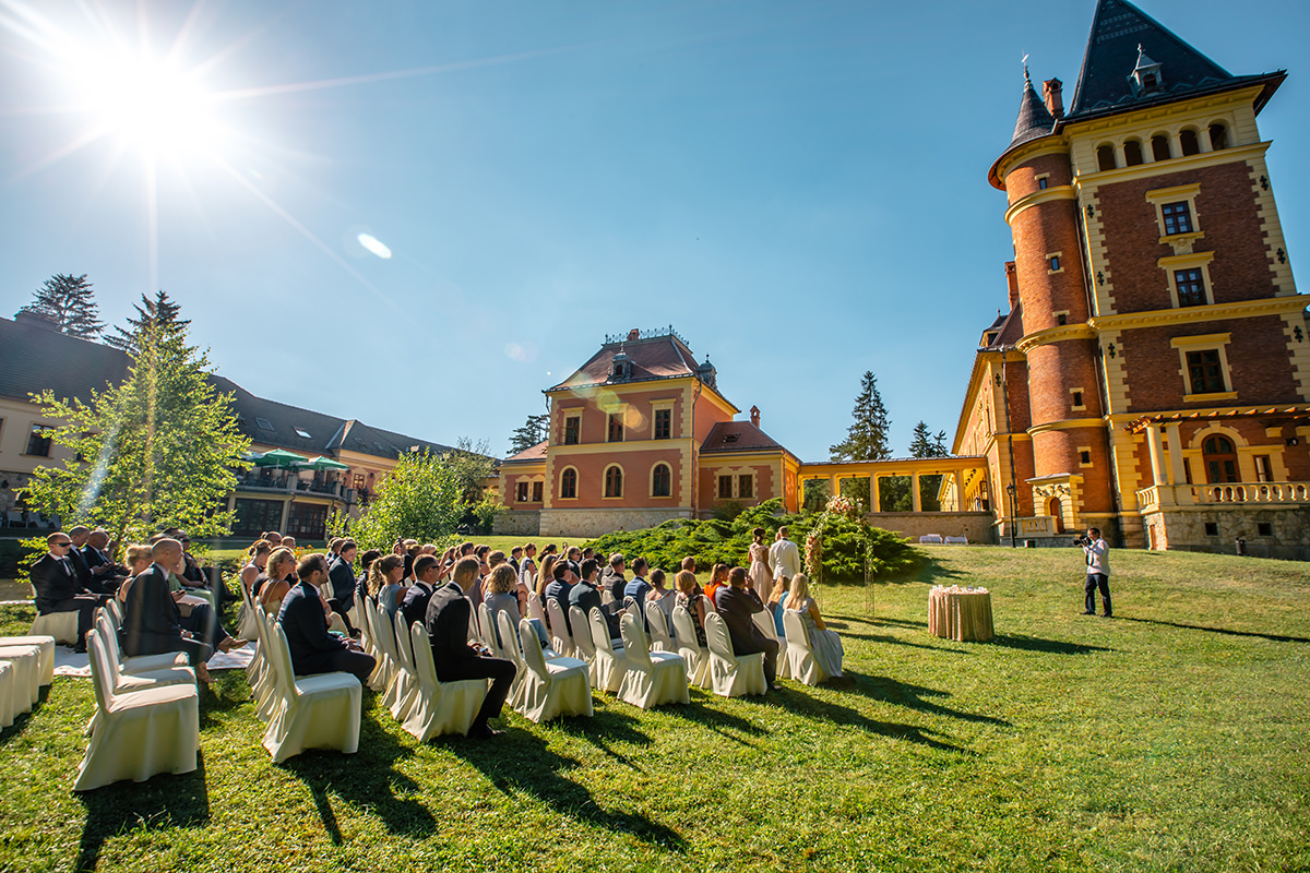 From other prospective the wedding ceremony set up with guests, bride and groom, celebrant and the Paradsasvar Castle Hotel in the background. Beautiful weather for a perfect wedding